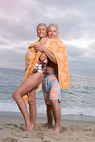 Mature couple wrapped in towel, embracing on beach, smiling, portrait, low angle view
