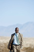 Businessman walking in desert, smiling, portrait