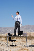 Businessman standing on desk in desert, holding telephone and receiver