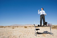 Businessman standing on desk in desert, holding telephone and receiver, low angle view
