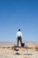 Businessman standing on desk in desert, rear view