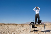 Businessman standing on desk in desert, using binoculars, low angle view (thumbnail)
