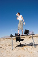 Businesswoman standing on desk in desert, shouting into telephone receiver, low angle view (thumbnail)