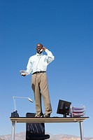 Businessman standing on desk in desert, using telephone, low angle view