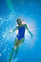 Woman in swimming pool, underwater view lens flare