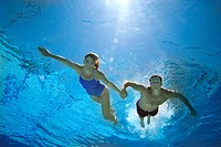Couple holding hands in swimming pool, underwater view lens flare