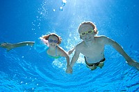 Boy and girl 8-12 holding hands in swimming pool, smiling, portrait, underwater view