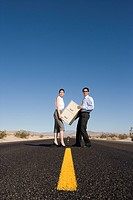 Businessman and woman with filing cabinet on road in desert