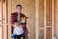 Builder with drill in partially built house, portrait