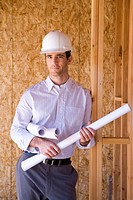 Architect with blueprints in hardhat in partially built house, portrait