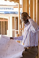 Businessman with blueprint in partially built house, using mobile phone, portrait