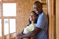 Couple in partially built house, man embracing woman, smiling, portrait