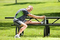 Mature man stretching on park bench, smiling, portrait (thumbnail)