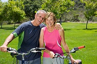 Mature couple with bicycles outdoors, man with arm around woman, smiling, portrait