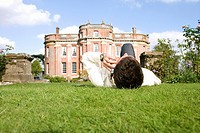 Young man lying on grass using mobile phone by manor house, ground view (thumbnail)
