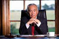 Mature businessman at desk, chin on hands, portrait (thumbnail)