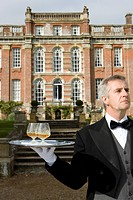 Mature butler with drinks on tray by manor house, close-up