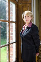 Mature businesswoman looking out window, portrait
