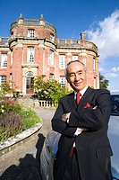 Businessman with arms crossed by manor house, portrait, low angle view
