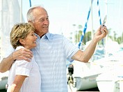 Senior couple arm in arm by boats, taking photograph of themselves, side view