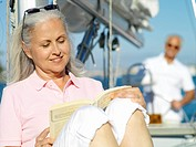 Mature woman reading book on boat, man in background