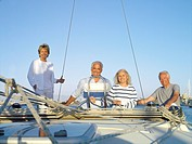 Mature couple at wheel of boat flanked by senior couple, smiling, portrait