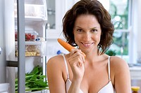 Young woman in underwear with carrot by open door of fridge, smiling, portrait