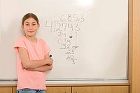 Girl 10-12 by equation on whiteboard in classroom, portrait