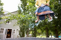 Girl 9-11 playing on trampoline in garden, low section