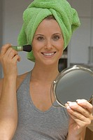 Woman with make-up brush and hand mirror