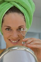 Woman with eyelash curler and hand mirror