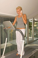 Woman on treadmill phoning