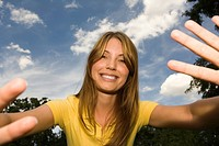 Young happy woman with arms out in park