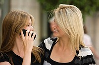 Young woman on cell phone with friend beside