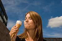 Young woman eating ice cream cone