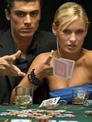 Couple throwing playing cards at poker game (thumbnail)