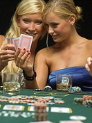 Women looking at playing cards at poker game