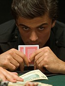 Intense man with playing cards at poker game