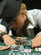 Woman in hat pushing poker chips