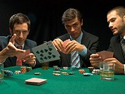 Men throwing playing cards at poker game