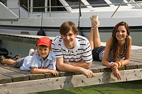 Young happy family laying on pier