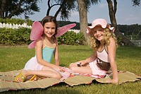 Young girls dressed up and sitting in yard