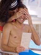 Woman covering man's eyes near pool (thumbnail)