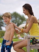 Mother putting sun lotion on son