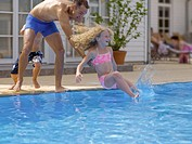 Father throwing daughter in pool