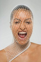 Portrait of a young woman shouting with a net over her face