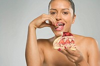 Portrait of a young woman eating a strawberry pie and smiling