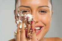 Portrait of a young woman eating cake icing and smiling (thumbnail)