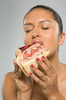Close-up of a young woman eating a strawberry pie