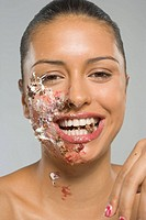 Portrait of a young woman eating cake icing